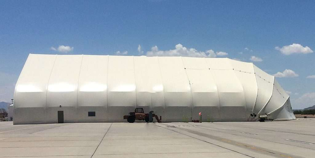 fabric aviation hangar with closed clamshell door on runway
