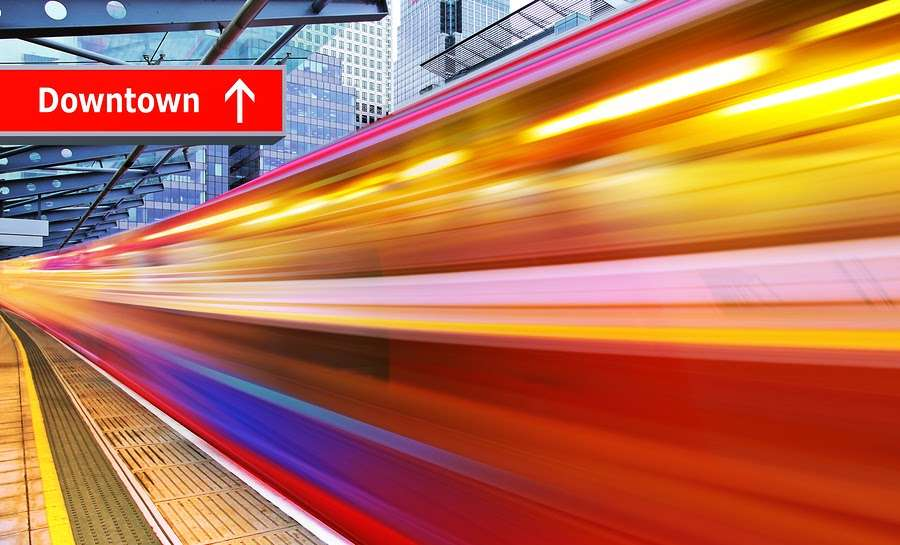 """bright lights of speeding train in uban train station with """"downtown"""" sign representing high speed rail development"""