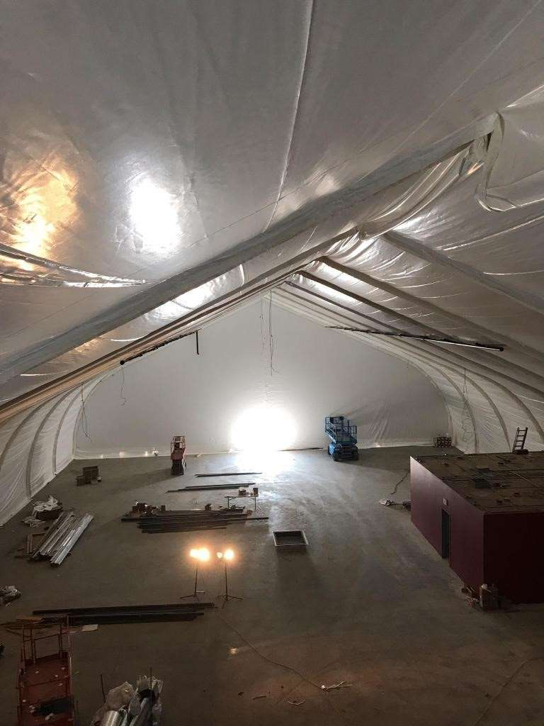 Fabric building interior insulation lining being installed during construction of  fabric building low cost homeless shelter solution in Pomona CA