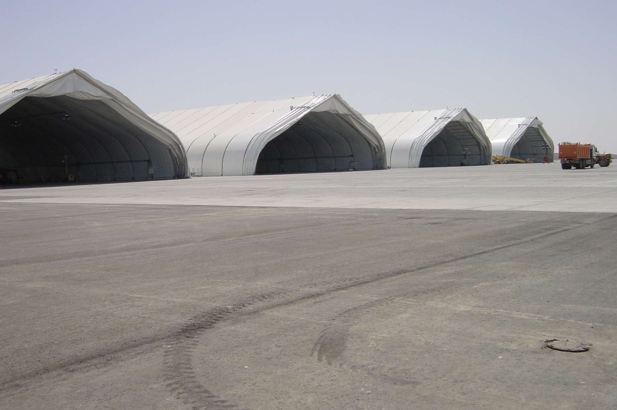 four fabric aircraft hangars for airplane fleet storage and maintenance operations on airport tarmac