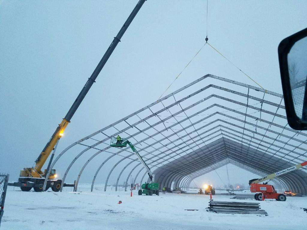 fabric green remediation structure being installed in winter with aluminum frame, crane lift and installation vehicles at work