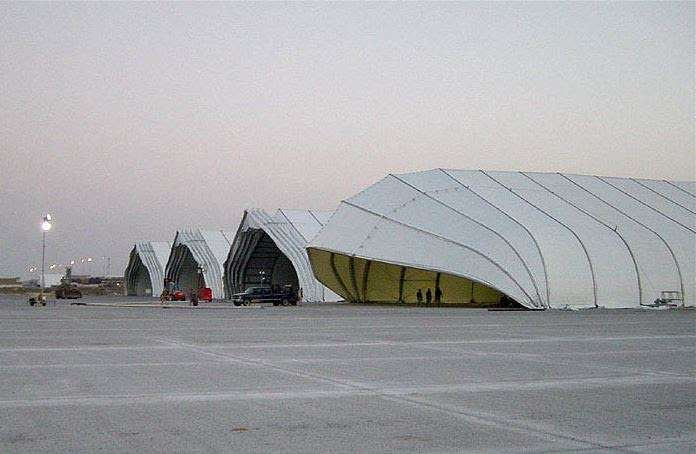 clamshell doors help insulate inside of row of energy efficient tension fabric aircraft hangars on airport tarmac