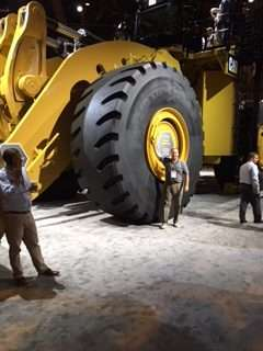 Allsite business manager next to huge tire on large mining equipment on display at MINExpo 2016
