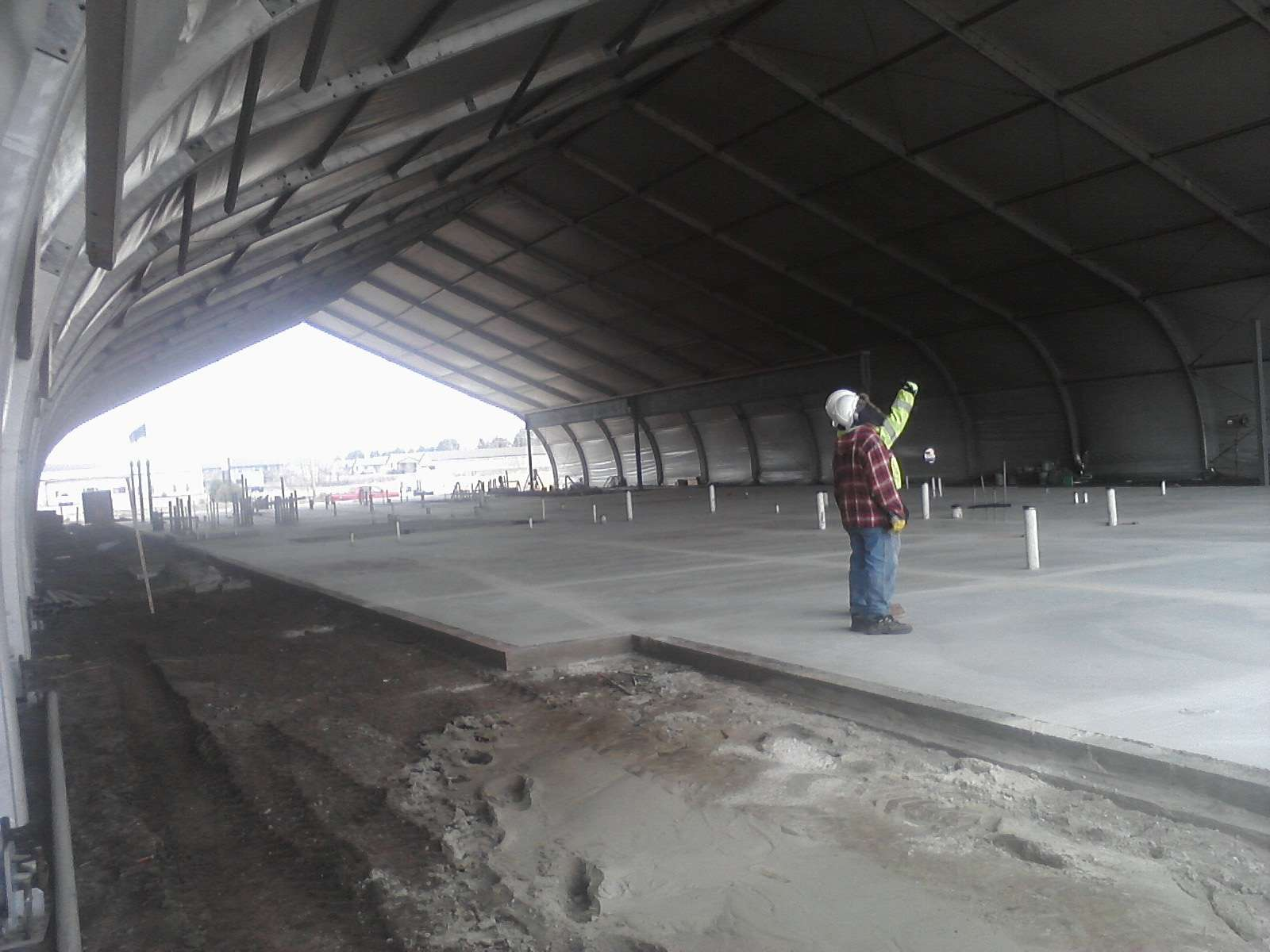 interior shot of large footprint tension fabric building under contsruction with engineers observing the process on concrete foundation