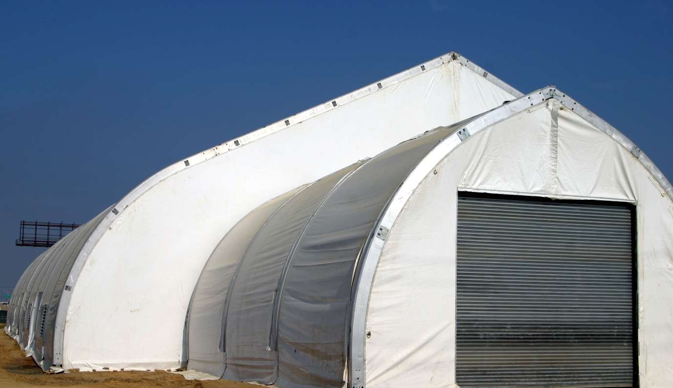 Fabric structure at gas fracking site with custom vestibule attachment
