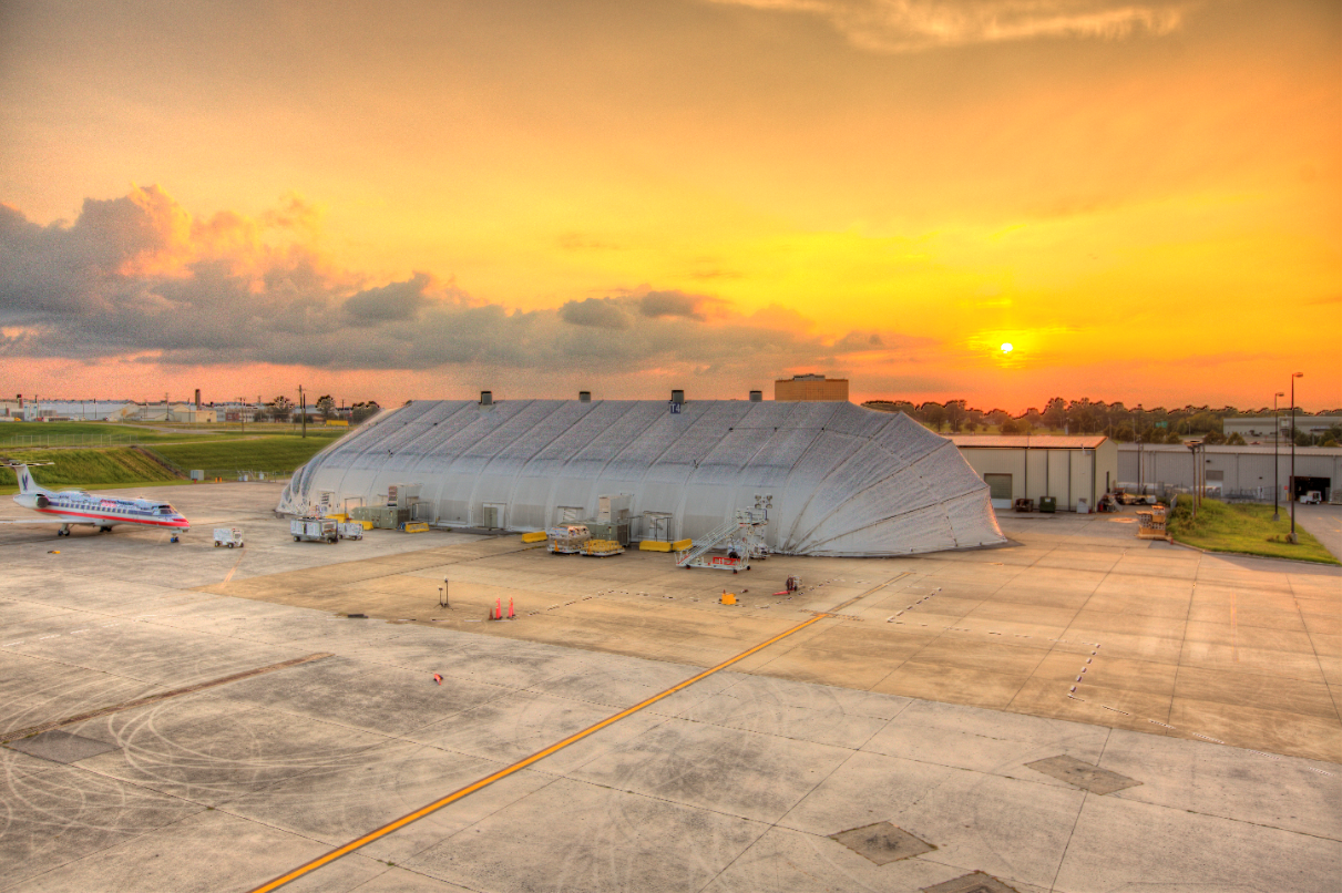 closed Allsite temporary fabric aviation hangar at sunset with airliner beside it