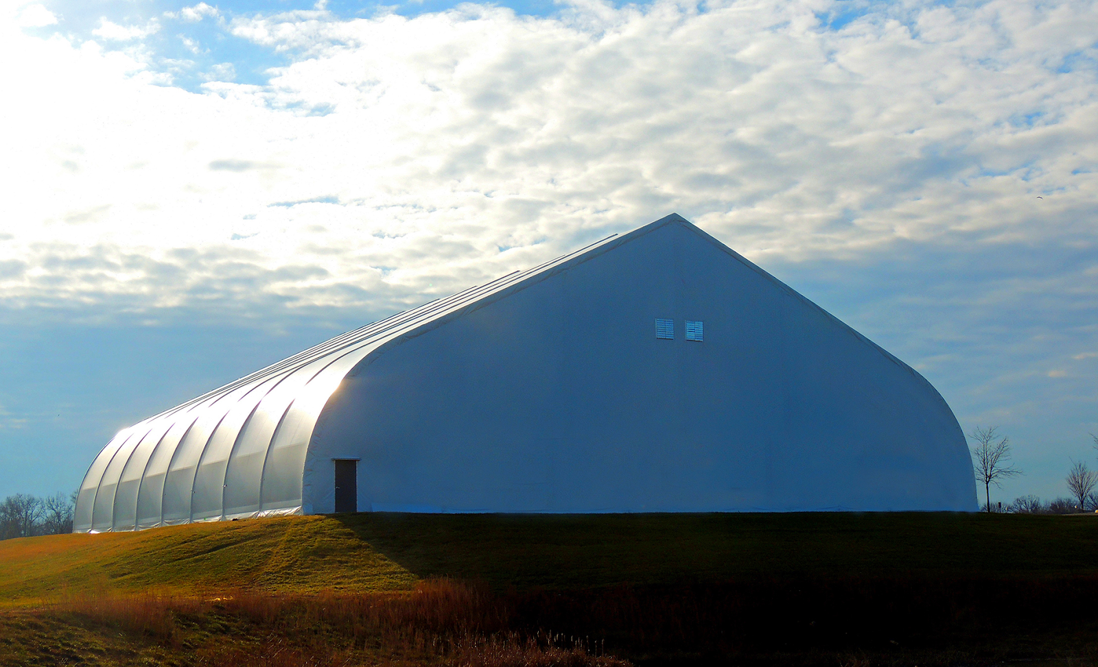 Exterior of tension fabric building housing cannabis crop in open field