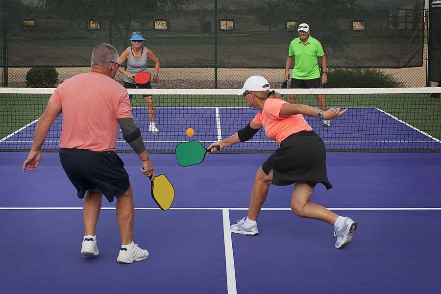 Colorful image of two teams playing Pickleball on an outdoor pickleball court