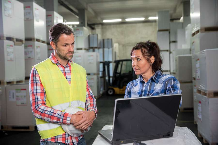 Man and woman working in warehouse on laptop surrounded by exceess inventory
