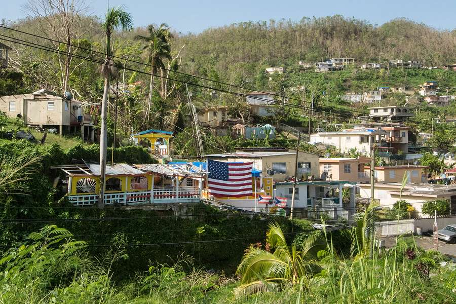 Puerto Rico town devastated by hurrican fallen trees damaged homes in need of humanitarian aid and flying an American flag