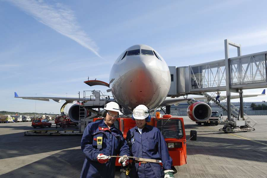 two airline mechanics in front of aircraft at the gate reviewing maintenance records