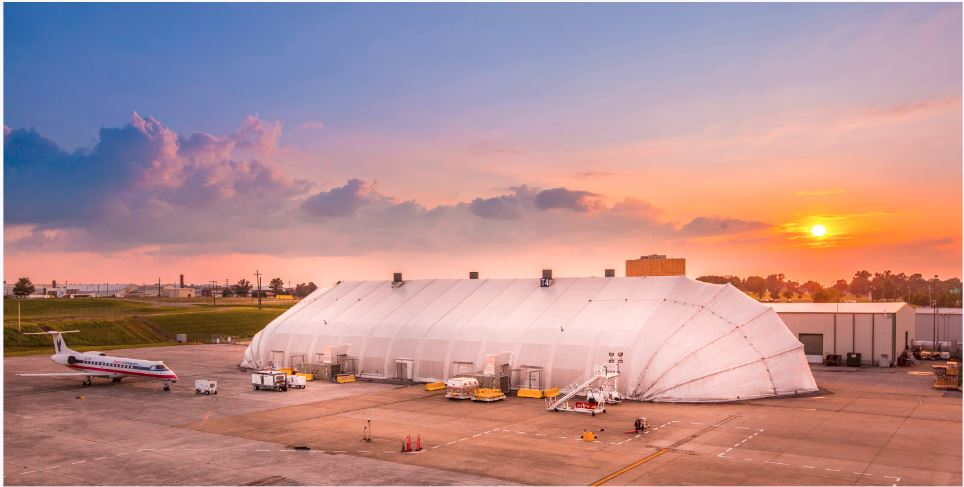 Allsite tension fabric structure at airport on tarmac with clamshell doors. At sunset.