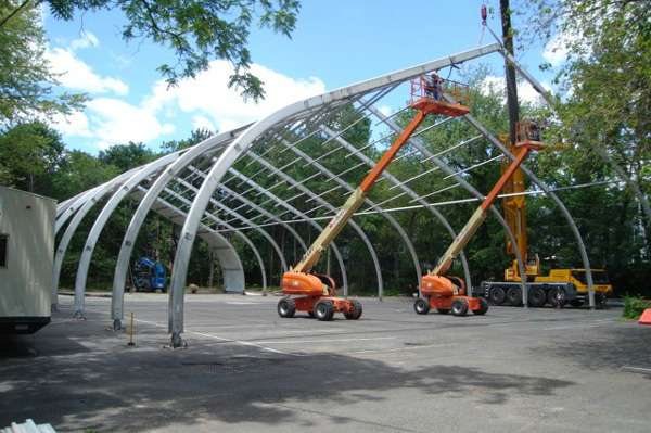 aluminum-framed fabric structure under construction installing the aluminum beams of the frame