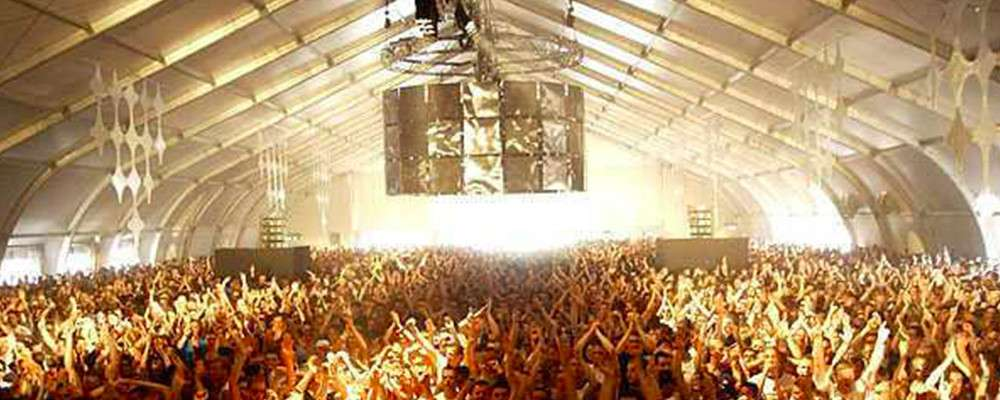 large crowd enjoying a concert inside a high ceiling tension fabric temporary event structure