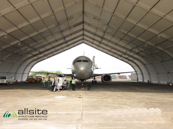 Jetstar aircraft in AOG service bay inside TFS hangar surrounded by mechanics