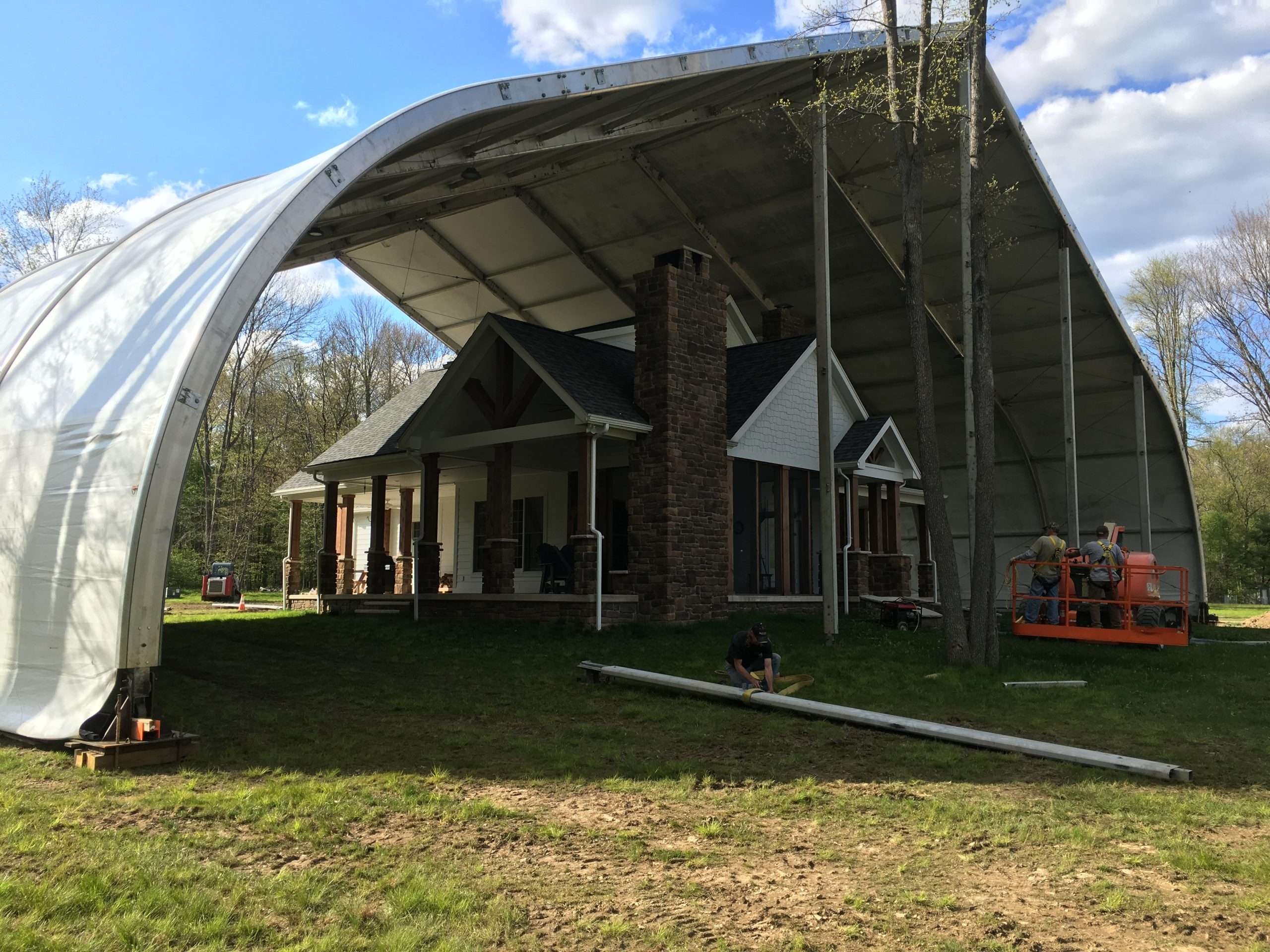 Construction shelter tension fabric structure protects large home from weather during renovation