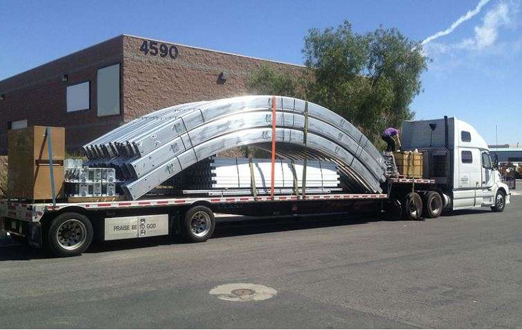 tension fabric building aluminum frame beams on a transport truck in front of a school building to be used as a large fabric school sports facility