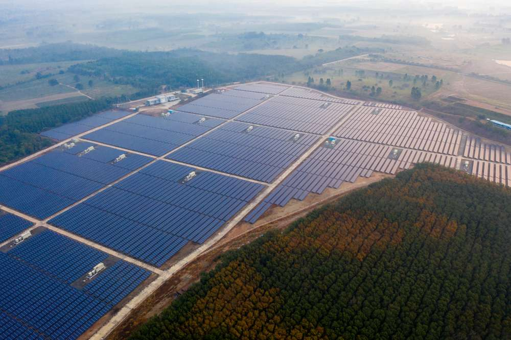 Large solar farm in rural area with panels across the landscape and a power processing facility feeding the energy grid representing growth of large scale solar energy production