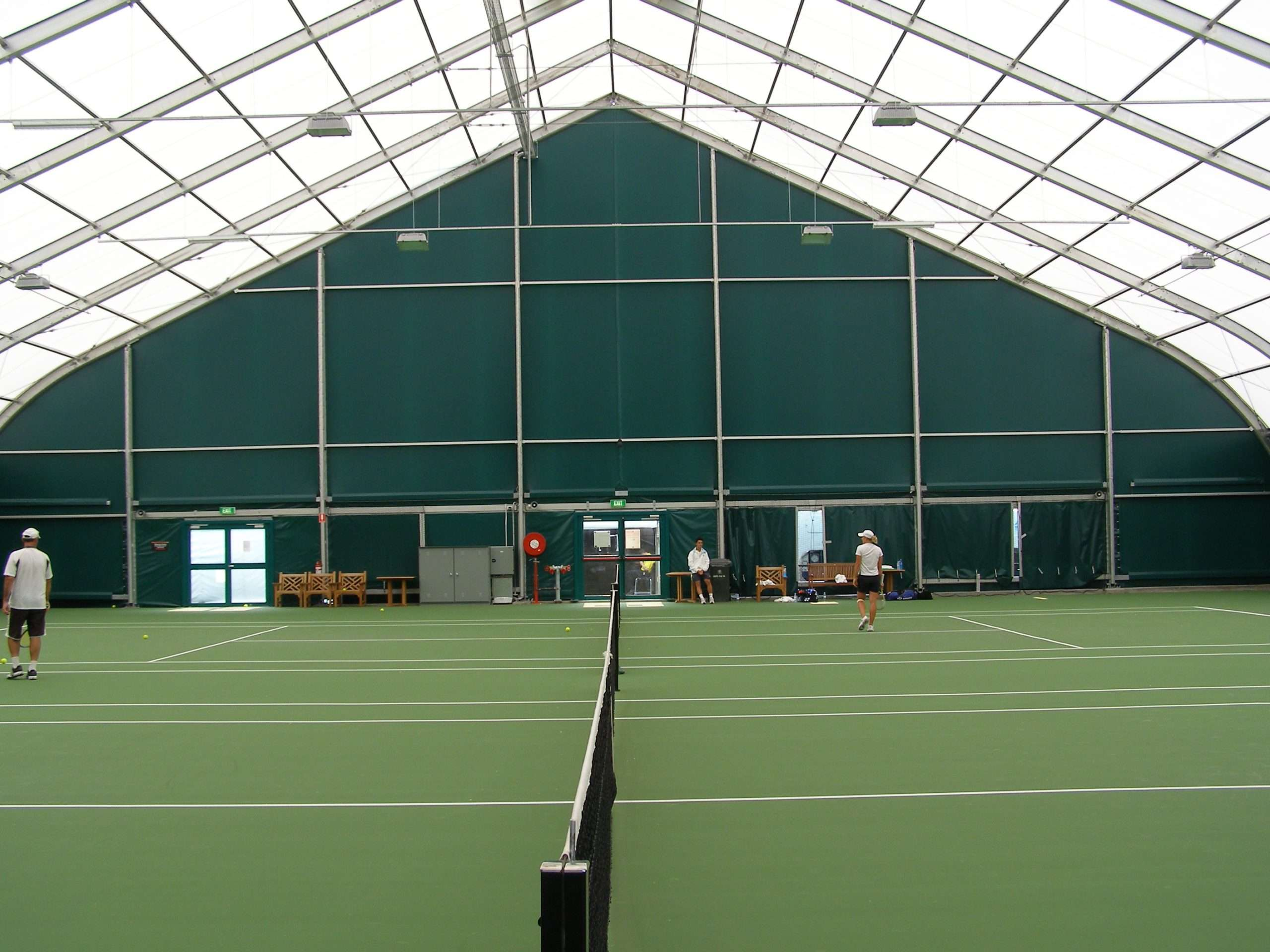 Bright and airy indoor tennis venue in an engineered fabric building showing tennis courts and high open ceiling