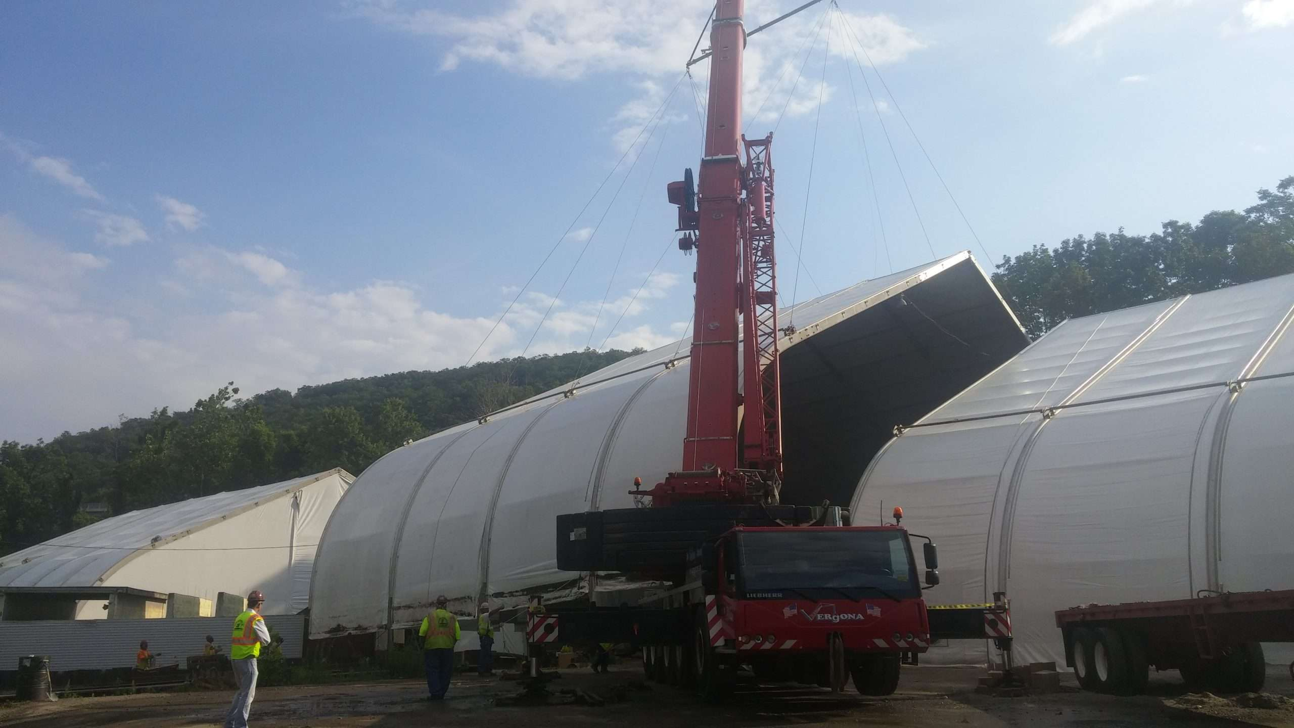engineered fabric structure segment being moved with a crane as engineers watch the building being reconfigured
