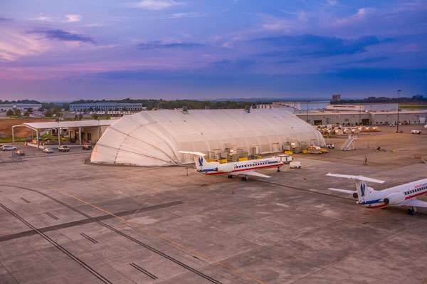 aerial view of tension fabric aircraft storage hangar with clamshell doors at airport with aircraft parked nearby