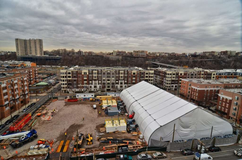Allsite Fabric Structure in large urban lot at land remediation project site surrounded by work equipment