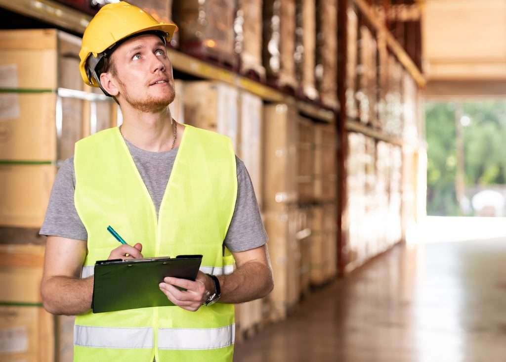 male warehouse worker with clipboard surveying stock along shelves inside large warehouse structure