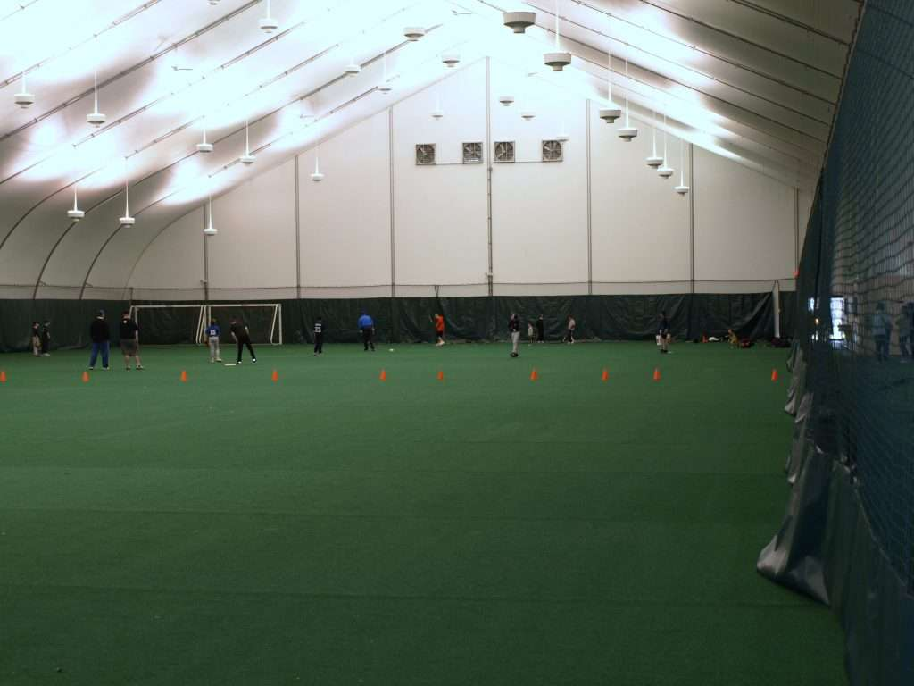 Interior spacious high ceiling tension fabric school sports building with baseball game being played at far end