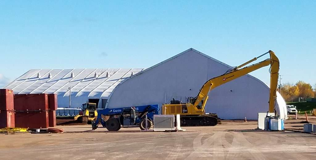 Exterior of an Allsite Tension Fabric Building with bulldozer and storage containers outside useful for emergency services operations center