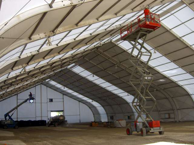 Tension Fabric building being assembled with workers on lifts working on attaching lighting on the ceiling for use as an emergency service building