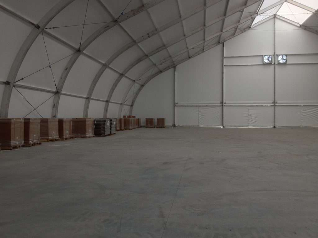 Allsite TFS interior open floor for warehouse or agriculture use, with storage crates along one one and ventilation fans in ceiling