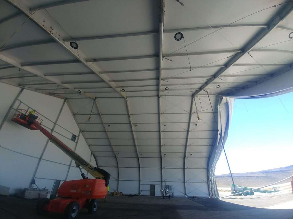 installing ventilation fan in interior of high ceiling fabric structure