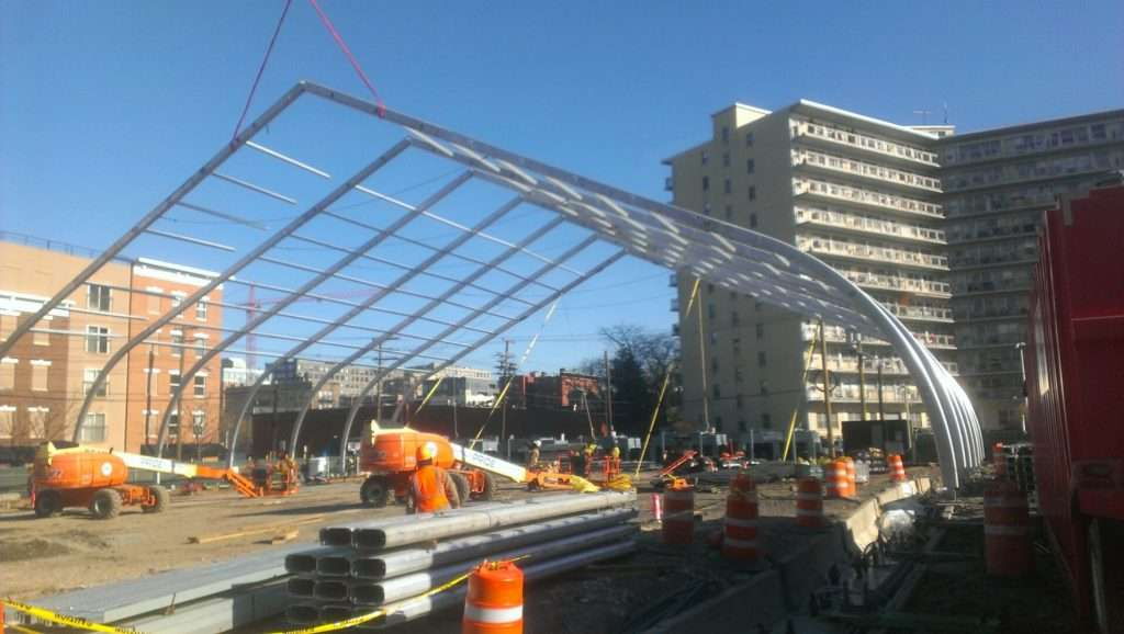 Raising arches of aluminum frame for large fabric structure on urban lot with workers carrying beams
