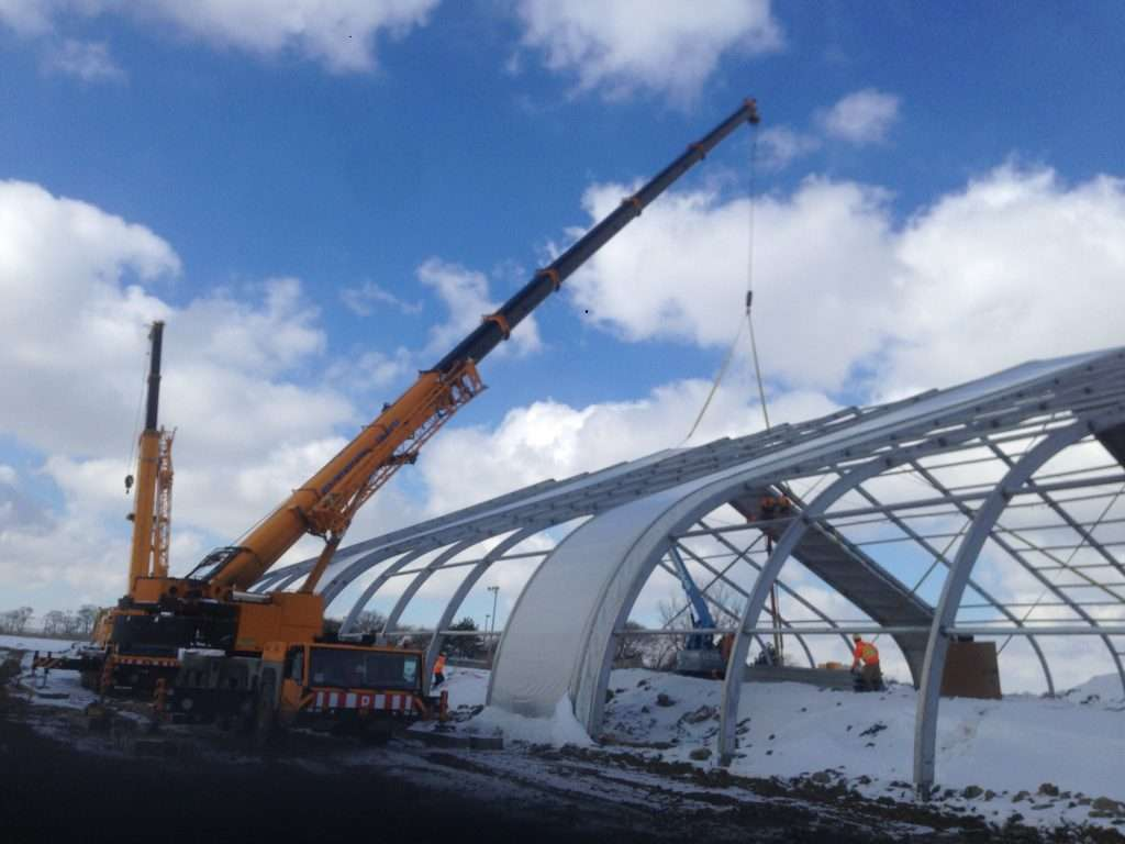 crane in the snow installing modular fabric panels on Allsite tension fabric structure