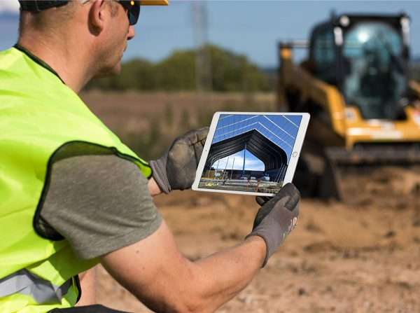 man looking at tension fabric structure on a tablet